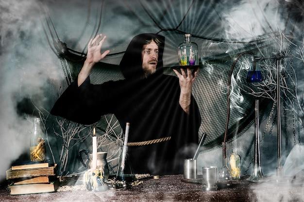 De middeleeuwse alchemist maakt een magisch ritueel aan tafel in zijn rooklaboratorium.