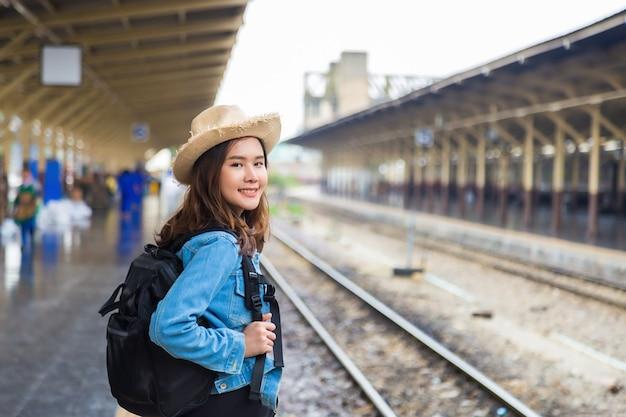 De middelgrote dichte omhooggaande jonge vrouw van de portret achterkant in jeansjasje die een rugzak dragen
