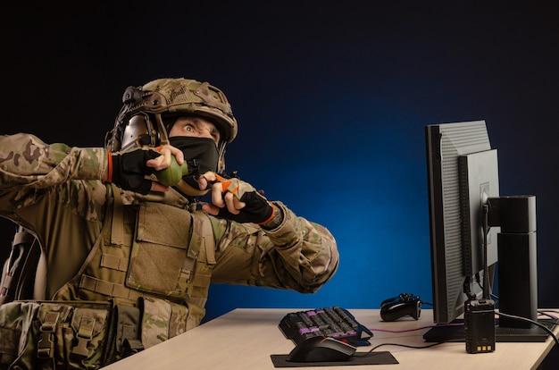 De militairen in uniform die achter een computer zitten zijn cyberoorlog, spelen, gooien een granaat