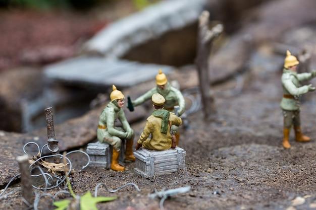 De militairen van het begin van de 20e eeuw staan stil bij de loopgraven, soldaten, miniatuurscène buiten, europa. minifiguren met hoge detaling van objecten, realistisch diorama, speelgoedmodel