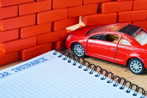 De miniatuur rode auto verpletterde in een bakstenen muur en autoverzekeringsvorm
