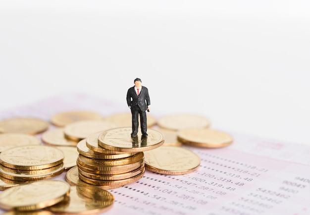 De miniatuur succesvolle zakenmanmensen bevinden zich bovenop gouden muntstukken met de achtergrond van de boekbank