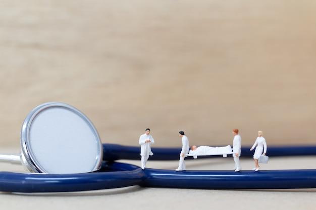De miniatuurarts met verpleegster draagt de patiënt op een brancard