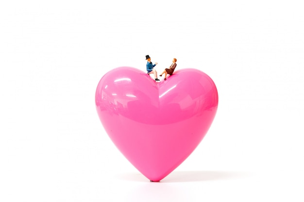 De miniatuurmensen koppelen aan roze hart op witte achtergrond