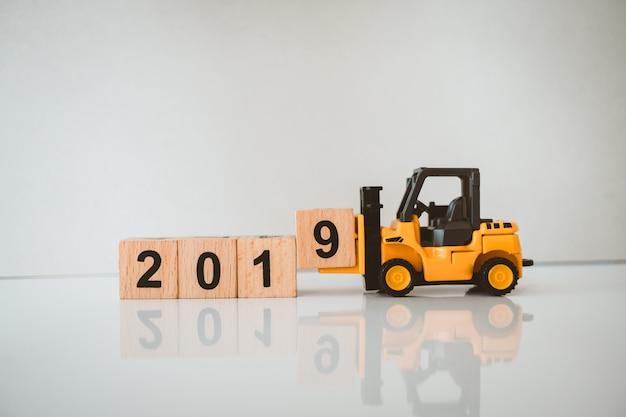 De miniatuurvorkheftruck heft het houten blok van jaar 2019 op gebruikend als bedrijfs en industrieconcept