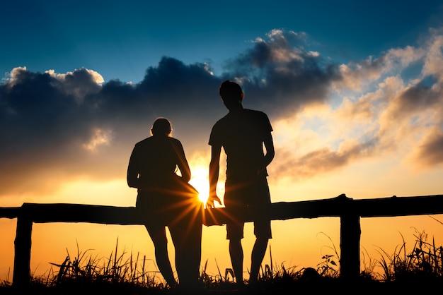 De minnaar van het silhouetpaar met bergenlandschap in mooie zonsonderganghemel