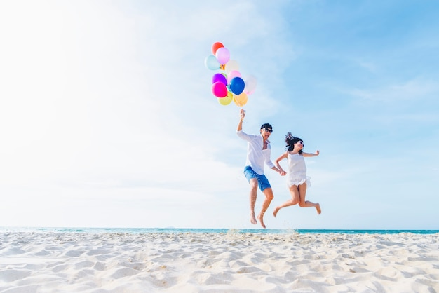 De minnaarspaar die van het geluk kleurrijke ballons houden en op het strand in zonnige dag springen