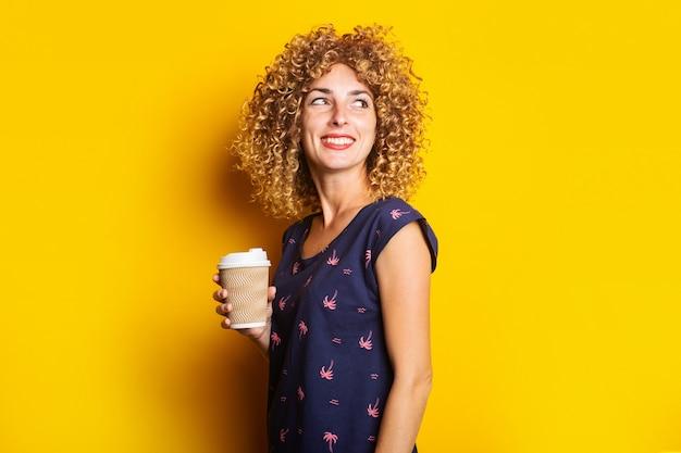 De minzame jonge vrouw met krullend haar houdt een kartonnen beker op een gele ondergrond