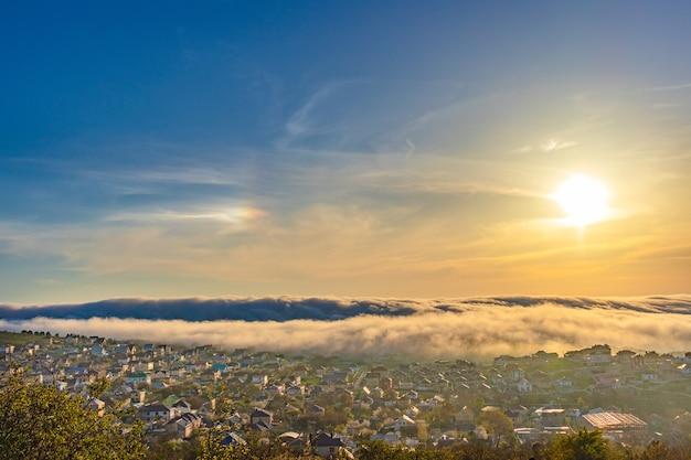 De mist hangt laag boven de stad. zonsondergang met mist over de stad, mooi landschap rusland, krasnodar krai, omgeving van de badplaats anapa