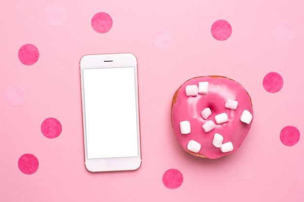 De mobiele telefoon en de zoete roze doughnut met heemst op een roze vlakte als achtergrond lagen