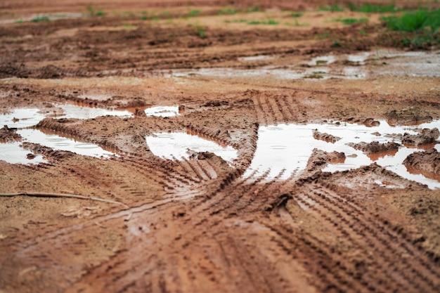 De modder op de grond met de wielsporen van de auto.