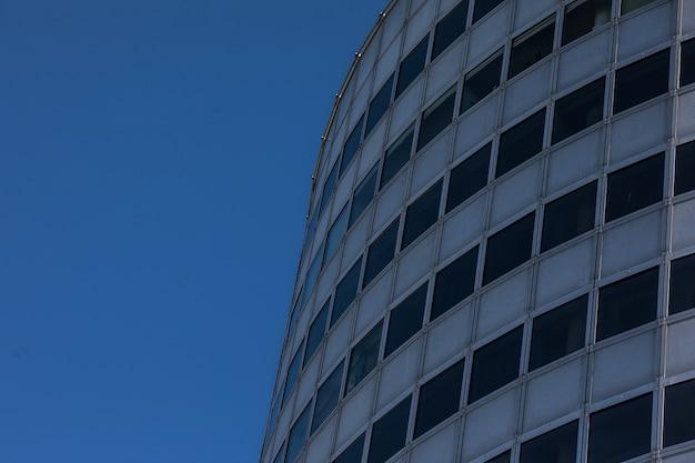 De moderne achtergrond van de glaswolkenkrabber met hemel en wolkenbezinning