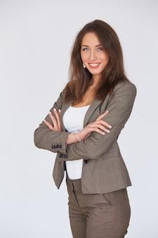 De moderne bedrijfsvrouw in kostuum met haar wapens kruiste status op grijze achtergrond.