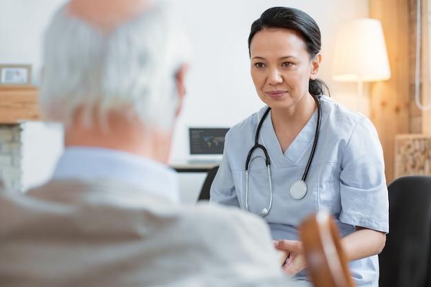 De moderne geneeskunde. geconcentreerde aziatische dokter staren naar senior man terwijl het dragen van uniform en zittend