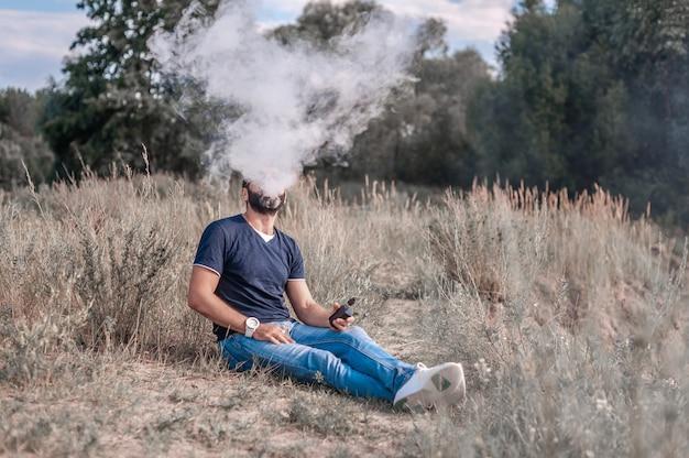 De moderne mens rust op het gras en vapen en blaast stoom af van een elektronische sigaret.