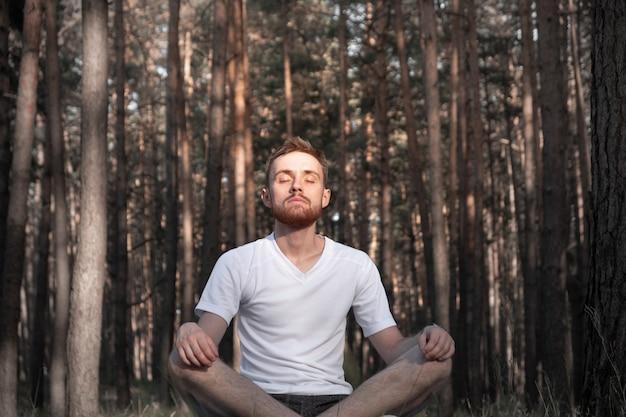 De moderne mens zit in het dennenbos met gesloten ogen en geniet van de stilte van de natuur
