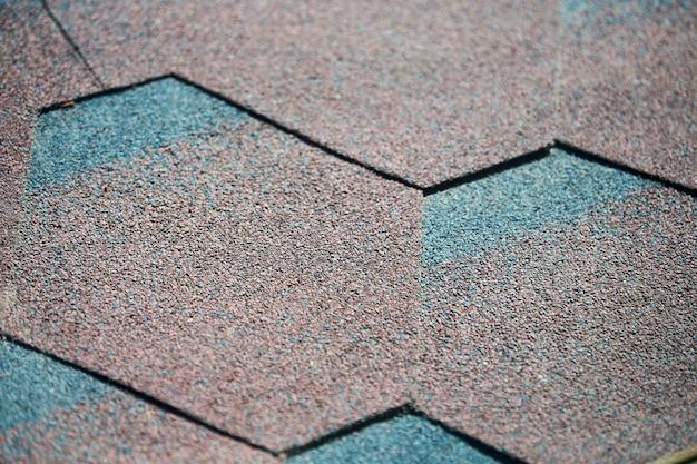De moderne tegels van dakdakspanen, sluiten omhoog. zachte asfalt dak achtergrond. nieuwe dakconstructie. gemakkelijke dakreparatie.