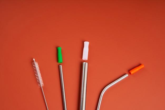 De moderne trend met zorg voor het milieu. zelfkit van herbruikbare metalen drankrietjes van verschillende diameters en vormen met schoonmaakgereedschap en siliconen doppen.