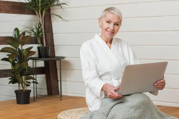 De moderne vrouw die van vooraanzichtsmiley op laptop kijkt