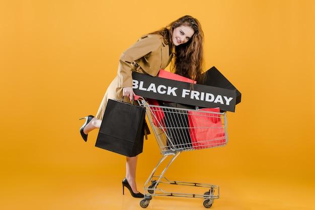 De modieuze jonge vrouw heeft handkar en zwart vrijdagteken met kleurrijke die het winkelen zakken en signaalband over geel wordt geïsoleerd