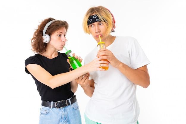 De modieuze kaukasische blondeman en de jonge vrouw drinken sap en luisteren aan muziek die op witte muur wordt geïsoleerd