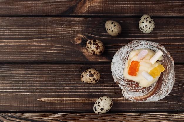 De modieuze pasen-cake met heemst en gelei draagt op een donkere rustieke houten achtergrond.