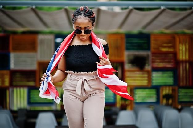 De modieuze vrouw in zonnebril stelde openlucht met de vlag van de vs