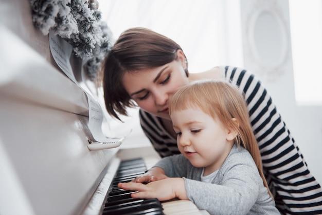 De moeder en de dochter die witte piano spelen, sluiten omhoog wiew