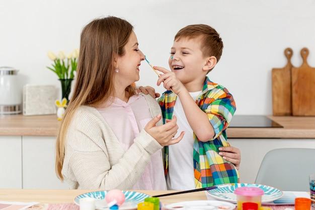 De moeder en de zoon van smiley het schilderen eieren
