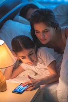 De moeder en dochter bellen in het bed. nachttijd