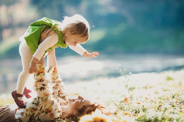 De moeder en dochter liggen op het gras