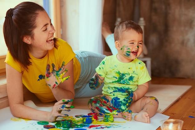 De moeder en zoon schilderen een groot papier met hun handen