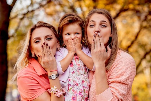 De moeder en zus brengen een klein meisje in verlegenheid