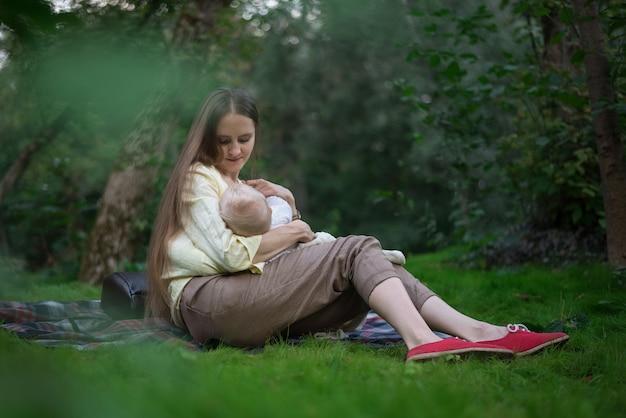 De moeder geeft baby de borst en houdt hem in wapens en het glimlachen. picknick met pasgeboren