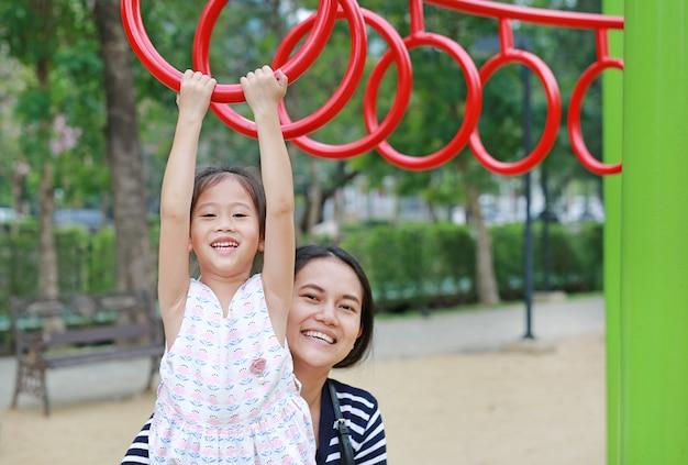 De moeder helpt haar dochter aan het spelen op gymnastiek- ring op speelplaats openlucht.