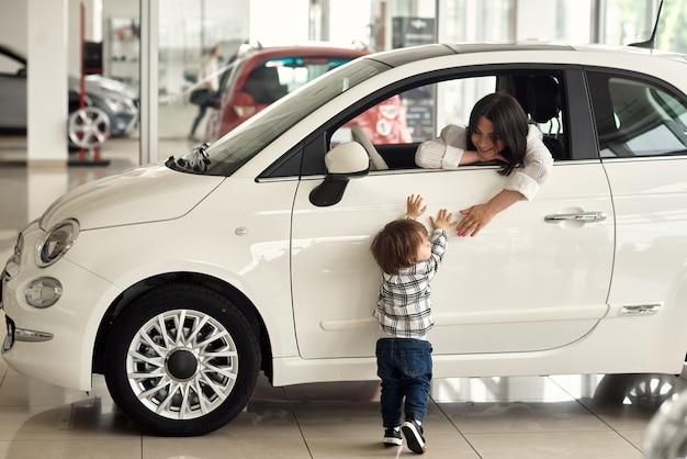De moeder kiest een auto waarin het handig is om haar zoontje te vervoeren.