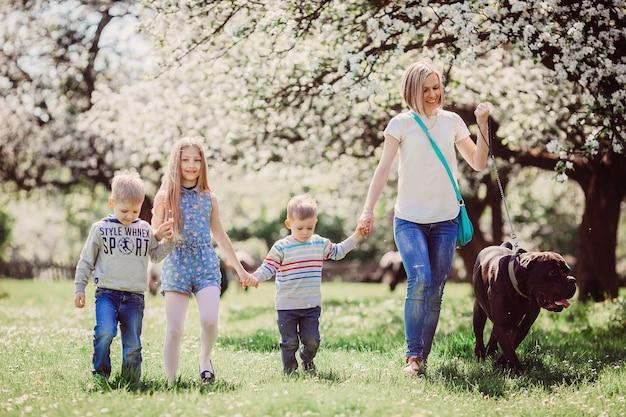 De moeder, kinderen en hond wandelen langs park