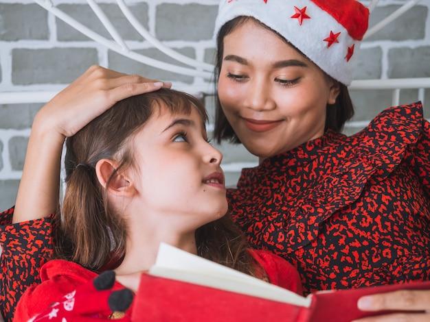 De moeder las een boek aan haar dochter op kerstmisdag, gelukkig familieconcept