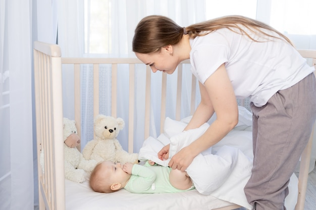 De moeder legt de baby te slapen in de wieg en bedekt hem met een deken