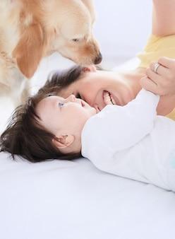 De moeder met dochter ligt op het bed en de hond kijkt naar hen