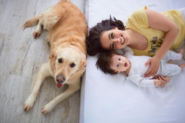 De moeder met dochter ligt op het bed en de hond zit in de buurt van bed