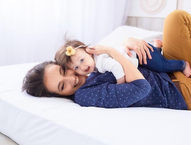 De moeder met dochter ligt op het bed