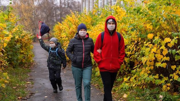 De moeder met twee zonen op straat met beschermende maskers, lopend