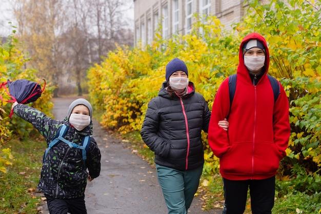 De moeder met twee zoons op straat met beschermende maskers, lopend