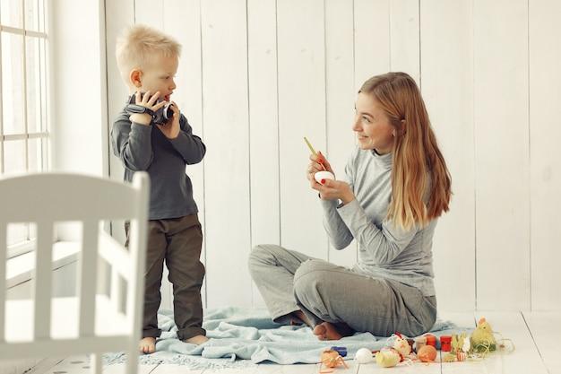 De moeder met zoon treft thuis aan pasen voorbereidingen