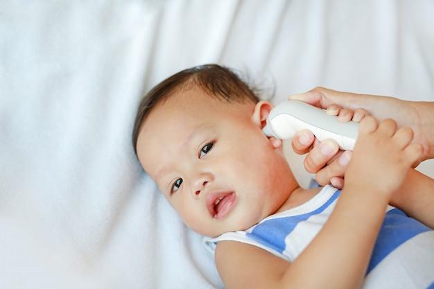 De moeder neemt temperatuur voor babyjongen met oorthermometer op bed thuis.