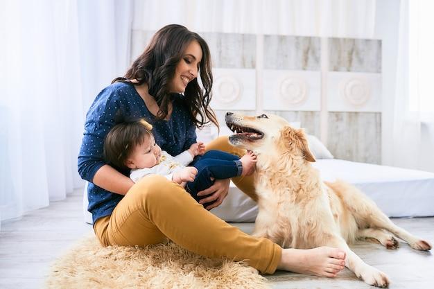 De moeder omhelst haar dochter en zit bij de hond