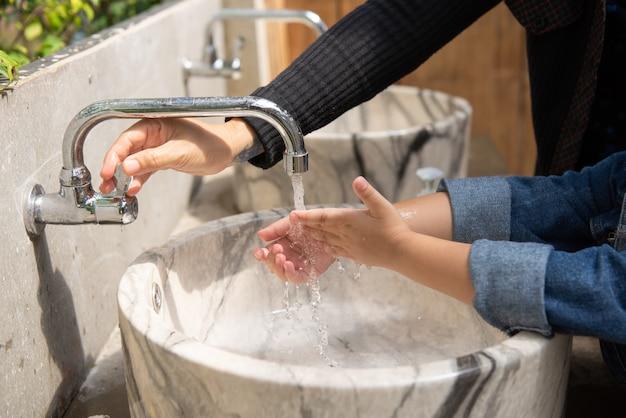 De moeder opent water voor dochter om handen in ton te wassen.