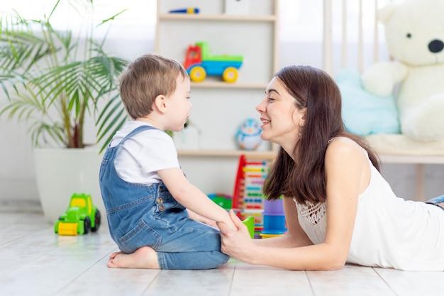 De moeder praat met het jongetje of speelt thuis met educatief speelgoed in de kinderkamer. een gelukkig, liefdevol gezin.