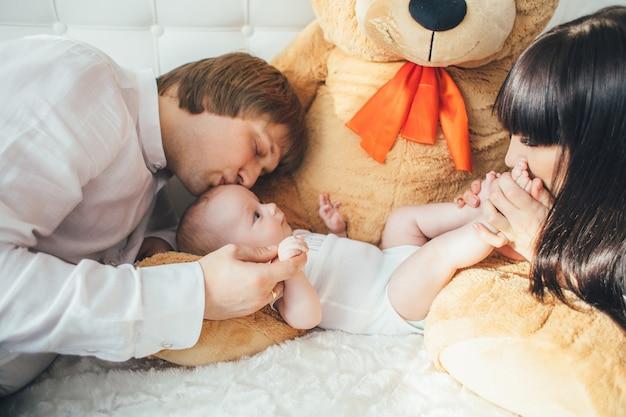 De moeder, vader en zoon liggen in de buurt van een beer op het bed
